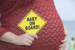 Pregnant woman with baby on board Stock Photos