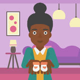 Pregnant woman with baby booties. An african-american pregnant woman holding baby booties in hands on the background of living room. Vector flat design stock illustration