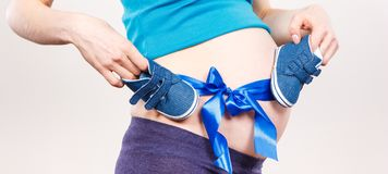 Pregnant woman with baby booties and blue ribbon, concept of expecting for newborn. Pregnant woman with baby booties and blue ribbon, concept of extending family stock image