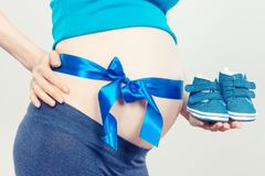 Pregnant woman with baby booties and blue ribbon, concept of expecting for newborn. Pregnant woman with baby booties and blue ribbon, concept of extending family stock photography