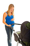 Pregnant woman with baby carriage Stock Image
