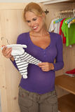 Pregnant woman with baby clothes. Pregnant woman longingly looking at the tiny babyclothes, that are ready in the closet Stock Photos