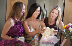 Pregnant Woman With Baby Clothes. Happy pregnant woman receives baby clothes as gift from her friend Stock Photo