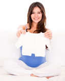 Pregnant woman with baby clothes Royalty Free Stock Images