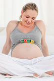Pregnant woman with baby cubes on her belly Stock Photos