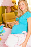 Pregnant woman in baby room Stock Image