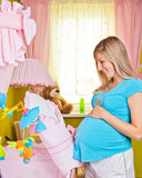Pregnant woman in baby room Stock Photo
