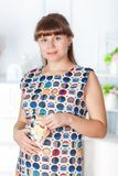 Pregnant woman with baby's bootees Stock Image