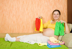 Pregnant woman with baby's clothes Stock Photography