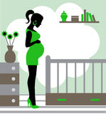 Pregnant woman in baby's room Royalty Free Stock Image