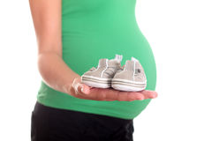 Pregnant woman and baby shoes Royalty Free Stock Photo
