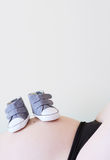 Pregnant woman with baby shoes Stock Photography