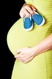 Pregnant woman with baby shoes Stock Photos