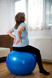 Pregnant woman with backache. Pregnant woman sitting on fit ball with backache at home stock image