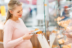 Pregnant woman with bag buying buns at grocery Stock Photography