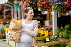 Pregnant woman with bag of food at street market Stock Photography