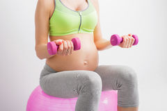 Pregnant woman on ball with dumbells Royalty Free Stock Photography