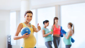 Pregnant woman with ball in gym showing thumbs up Royalty Free Stock Images