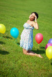 Pregnant woman with balloons on grass Royalty Free Stock Image