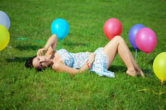 Pregnant woman with balloons on grass Royalty Free Stock Photos