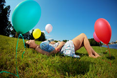 Pregnant woman with balloons on grass Stock Photo
