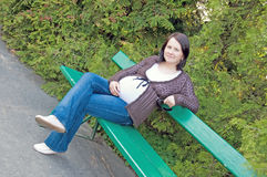 Pregnant woman at the bank. Pregnant woman sitting at the bank in the park stock image