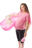 Pregnant woman bathe with toy Teddy bear in tub Royalty Free Stock Image