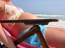 Pregnant Woman on Beach. A pregnant woman lying in the sun catching some rays Royalty Free Stock Photo