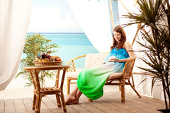 Pregnant woman on the beach in bungalow Stock Image