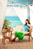 Pregnant woman on the beach in bungalow Stock Images