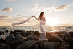 Pregnant Woman on the Beach with Flowing Veil Royalty Free Stock Photos
