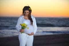Pregnant woman at the beach during sunset Royalty Free Stock Image