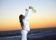Pregnant woman at the beach during sunset Stock Photo