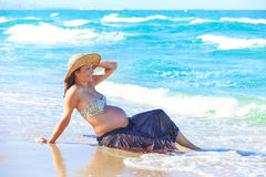 Pregnant woman on the beach with waves Royalty Free Stock Photo