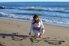 Pregnant woman at beach writing  baby in the sand Stock Photos