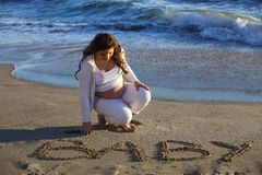 Pregnant woman at beach writing  baby in the sand Stock Image