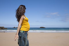 Pregnant woman at beach. Pregnant woman with yellow shirt at Asturian beach stock image