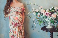Pregnant woman in beautiful colorful dress is standing next to bright bouquet of flowers and holds hands on belly at home interior. Pregnant woman in a beautiful royalty free stock image