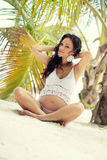 Pregnant woman in beautiful knit set on the sandy beach. Royalty Free Stock Image
