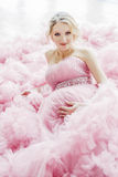 Pregnant woman in beautiful pink magnificent dress Stock Photos