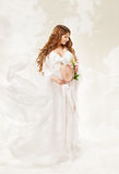 Pregnant woman. Beautiful pregnancy: long curly hair and chiffon Royalty Free Stock Images