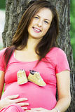 Pregnant woman. Beautiful pregneant woman smiling with baby shoes on her belly Royalty Free Stock Photos