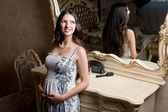Pregnant woman in bedroom near mirror Royalty Free Stock Images