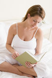 Pregnant woman in bedroom reading book Stock Images