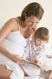 Pregnant woman in bedroom reading book Royalty Free Stock Image