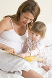 Pregnant woman in bedroom reading book with daught Stock Images