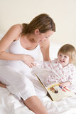 Pregnant woman in bedroom reading book with daught Royalty Free Stock Photos