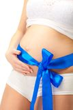 Pregnant woman belly with blue bow Royalty Free Stock Photo