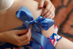 Pregnant woman. Belly with blue ribbon. Third trimester of pregnancy. Pregnant woman. Belly with blue ribbon closeup. Third trimester of pregnancy royalty free stock photos