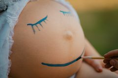 Pregnant woman belly closeup with smiling face drawing Royalty Free Stock Photos